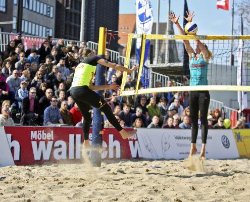 Beachvolleyballerin blockt Schlag im Sprung